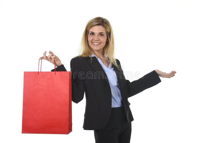 Νέα ευτυχής όμορφη γυναίκα στο επιχειρησιακό κοστούμι στη συγκινημένη έκφραση προσώπου που κρατά την κόκκινη τσάντα αγορών στοκ φωτογραφία