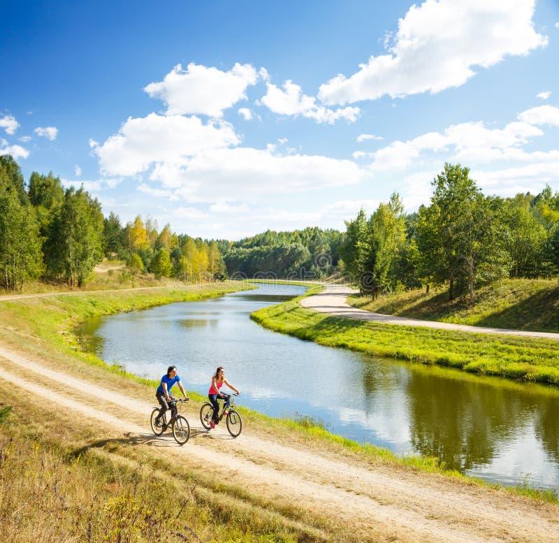 Νέα ευτυχή οδηγώντας ποδήλατα ζεύγους από τον ποταμό στοκ εικόνες