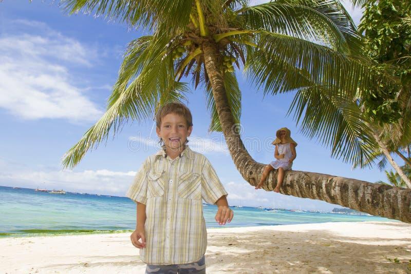 Νέα ευτυχή παιδιά - αγόρι και κορίτσι - στο τροπικό backgrou παραλιών στοκ εικόνες