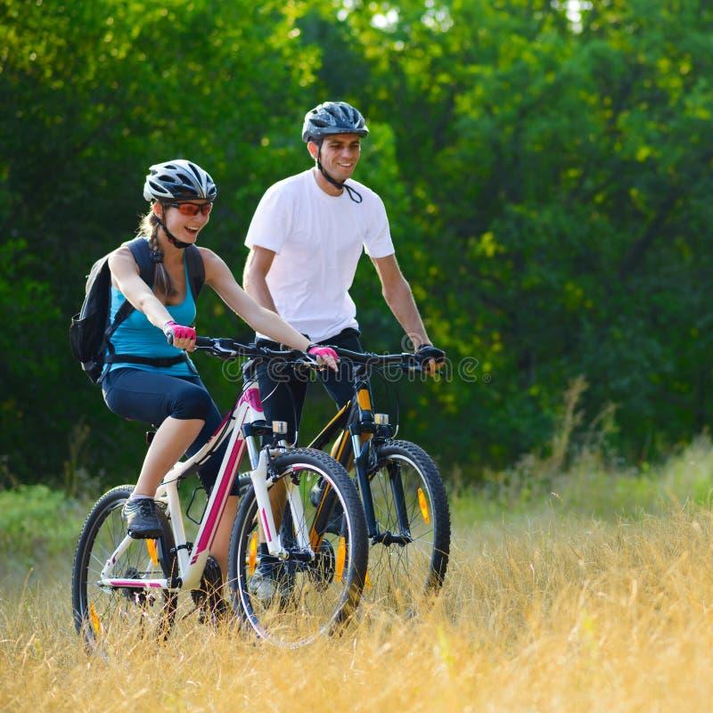 Νέα ευτυχή ποδήλατα βουνών ζεύγους οδηγώντας υπαίθρια στοκ εικόνες