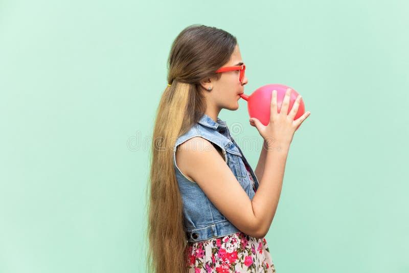 Νέα ευτυχή φυσώντας μπαλόνια κοριτσιών για τη γιορτή γενεθλίων, που εξετάζει αστεία τη κάμερα σε ένα ανοικτό πράσινο υπόβαθρο στοκ φωτογραφία