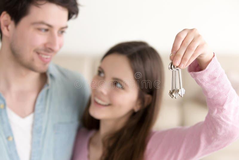 Νέα εύθυμα κλειδιά καινούργιων σπιτιών εκμετάλλευσης ζευγών, mortga ακίνητων περιουσιών στοκ φωτογραφία με δικαίωμα ελεύθερης χρήσης