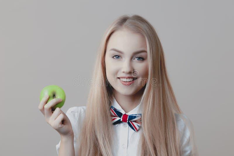 Νέα εύθυμα χαριτωμένα ξανθά χαμόγελα με το πράσινο μήλο στο χέρι της στοκ εικόνες με δικαίωμα ελεύθερης χρήσης