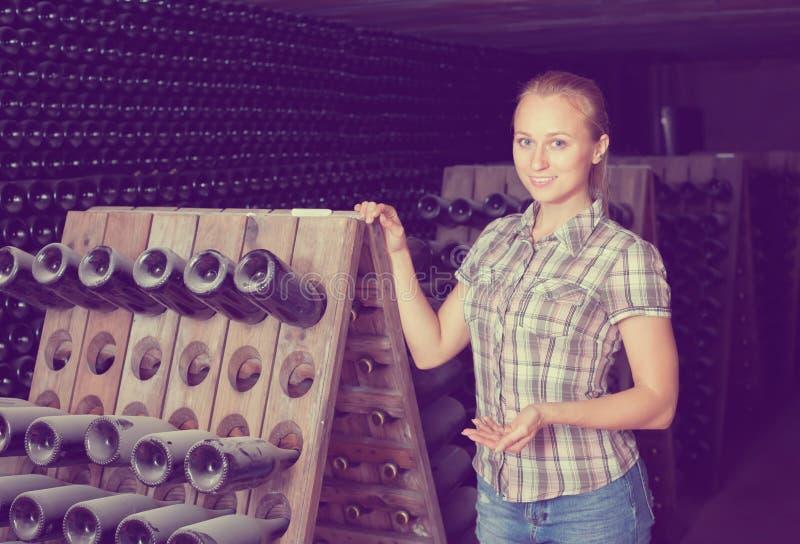 Νέα εύθυμη γυναίκα στο κελάρι με την αποθήκευση μπουκαλιών κρασιού στοκ εικόνες