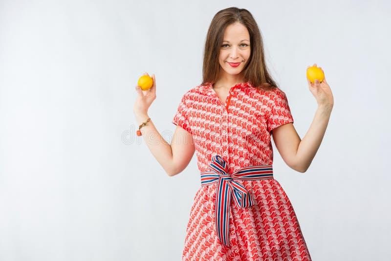 Νέα εύθυμη γυναίκα στο κόκκινο φόρεμα που κρατά δύο λεμόνια στοκ φωτογραφία με δικαίωμα ελεύθερης χρήσης