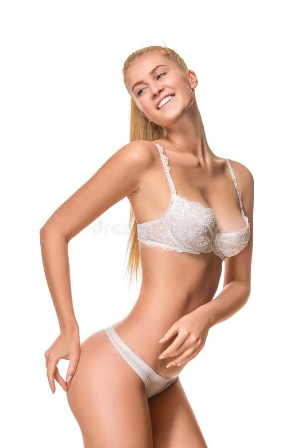 Download Νέα εύθυμη ξανθή γυναίκα που φορά το άσπρο εσώρουχο που απομονώνεται Στοκ Εικόνα - εικόνα από κιλότες, κυρία: 62701525