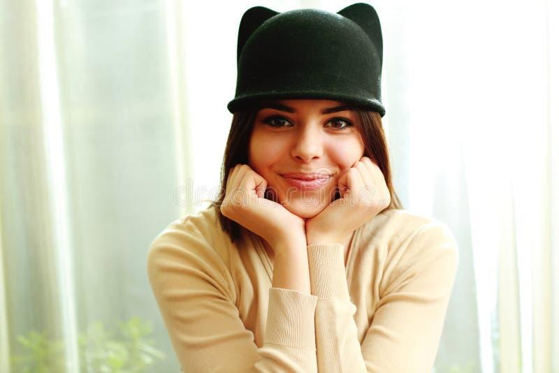 Νέα εύθυμη χαμογελώντας γυναίκα στο χαριτωμένο καπέλο στοκ φωτογραφίες