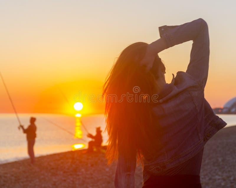 Νέα ελκυστική γυναίκα στην παραλία στο χρόνο ηλιοβασιλέματος στη σκηνή backlight στοκ εικόνες