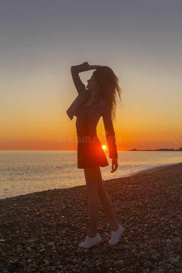 Νέα ελκυστική γυναίκα στην παραλία στο χρόνο ηλιοβασιλέματος στοκ εικόνες