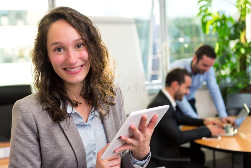 Νέα ελκυστική επιχειρηματίας που εργάζεται στο γραφείο με το associ στοκ εικόνες