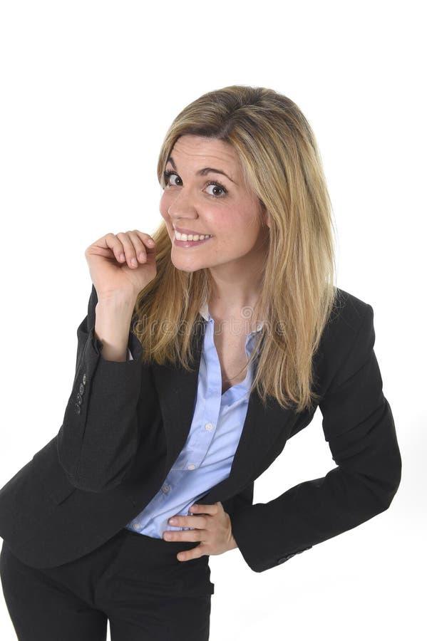 Νέα ελκυστική επιχειρησιακή γυναίκα με τα ξανθά μαλλιά που θέτουν το φιλικό χαμόγελο ευτυχές στοκ εικόνα