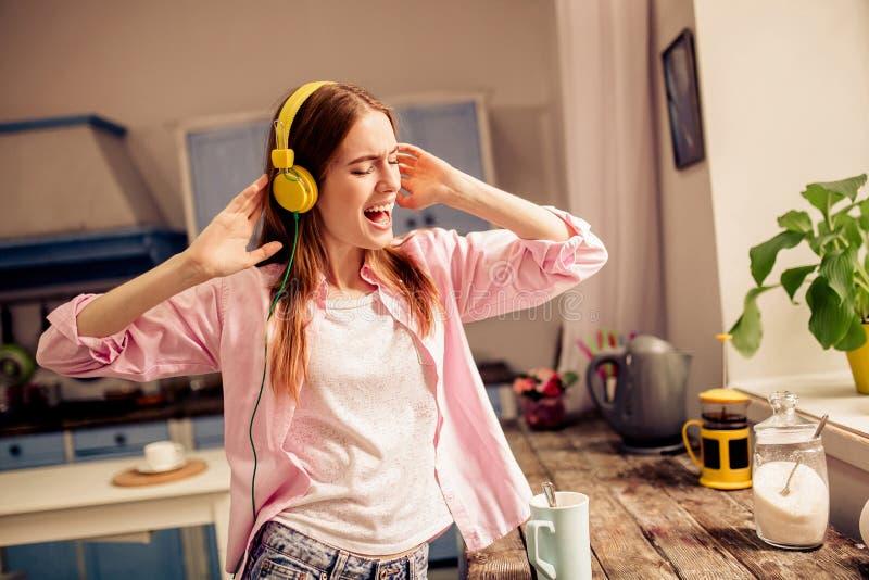 Νέα ελκυστική μουσική ακούσματος κοριτσιών στα ακουστικά στο σπίτι στοκ εικόνες με δικαίωμα ελεύθερης χρήσης