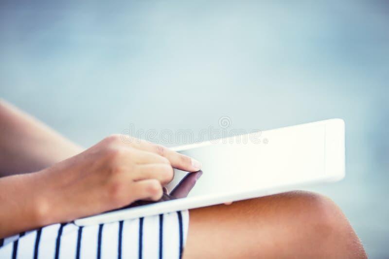 Νέα ελκυστική συνεδρίαση κοριτσιών με μια ταμπλέτα στα χέρια στοκ εικόνες