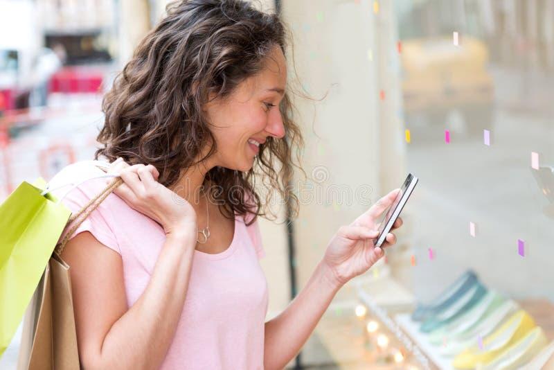 Νέα ελκυστική χρησιμοποίηση γυναικών κινητή κατά τη διάρκεια των αγορών στοκ φωτογραφίες