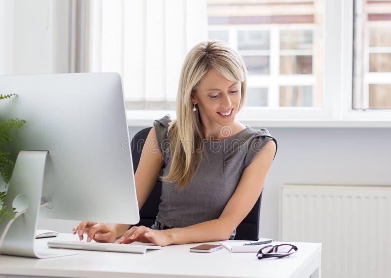 Νέα δημιουργική γυναίκα που εργάζεται με τον υπολογιστή στοκ εικόνα