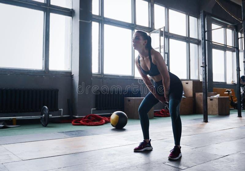 Νέα θηλυκή άσκηση ικανότητας με το κουδούνι κατσαρολών Καυκάσια γυναίκα που κάνει crossfit workout στη γυμναστική στοκ εικόνα με δικαίωμα ελεύθερης χρήσης