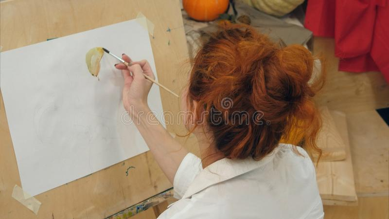 Νέα θηλυκή εικόνα watercolor ζωγραφικής καλλιτεχνών στο στούντιο στοκ εικόνες