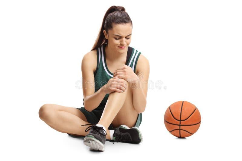 Νέα θηλυκή συνεδρίαση παίχτης μπάσκετ σε ένα πάτωμα και εκμετάλλευση  στοκ εικόνες με δικαίωμα ελεύθερης χρήσης