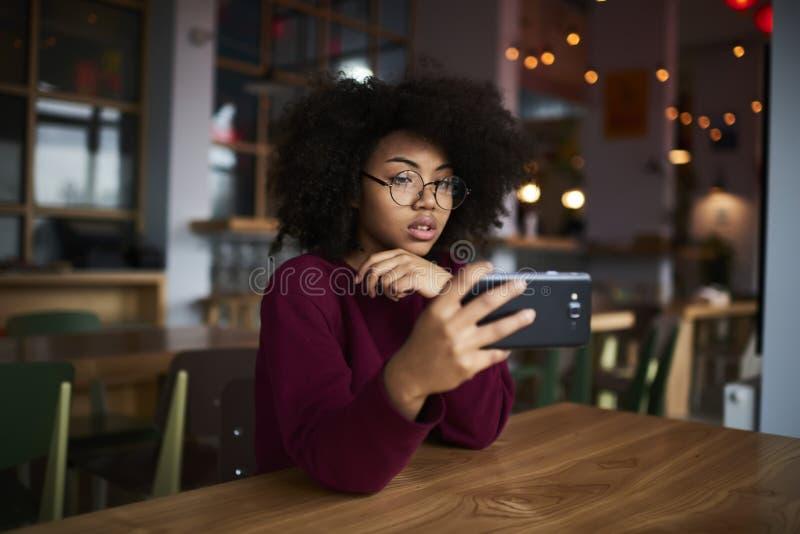 Νέα θηλυκή συνεδρίαση το διάστημα με το σύγχρονο smartphone στοκ εικόνες