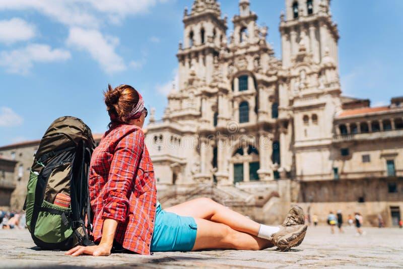 Νέα θηλυκή συνεδρίαση backpacker piligrim στο τετραγωνικό plaza Obradeiro στο Σαντιάγο de Compostela απεικόνιση αποθεμάτων