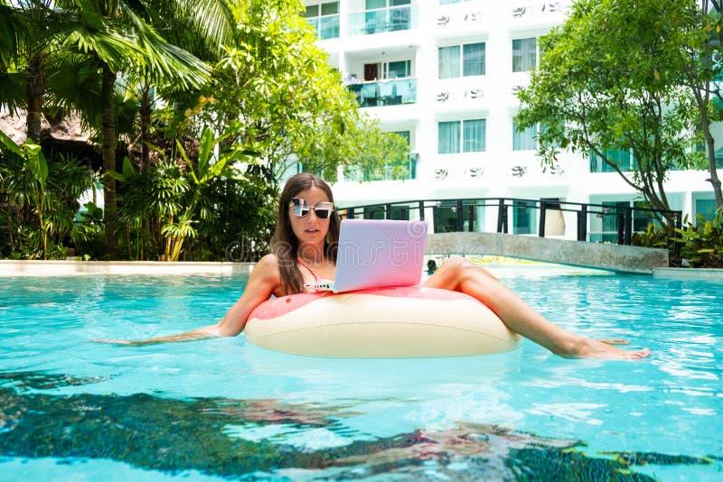 Νέα θηλυκή συνεδρίαση freelancer με ένα lap-top σε έναν διογκώσιμο κύκλο στη λίμνη Πολυάσχολος κατά τη διάρκεια των διακοπών Μακρ στοκ εικόνες