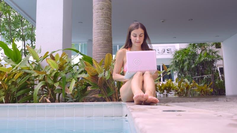 Νέα θηλυκή συνεδρίαση freelancer με το lap-top κοντά στη λίμνη E Πολυάσχολος κατά τη διάρκεια των διακοπών Η έννοια της μακρινής  στοκ φωτογραφία με δικαίωμα ελεύθερης χρήσης