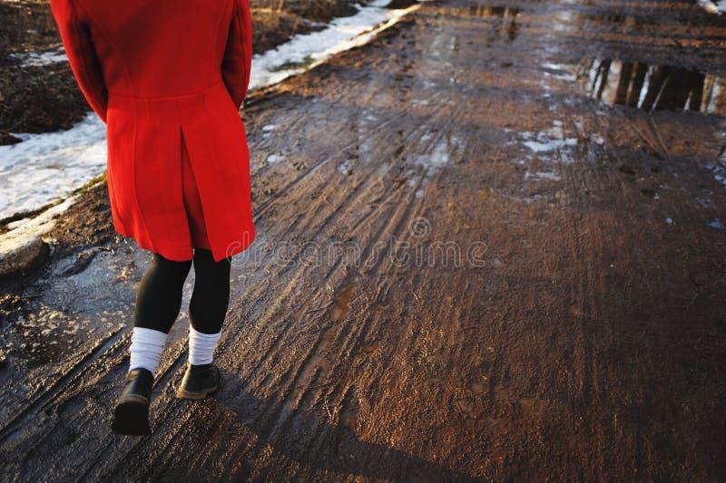 Νέα θηλυκά πόδια που περπατούν προς το ηλιοβασίλεμα σε έναν βρώμικο δρόμο την άνοιξη στοκ φωτογραφίες με δικαίωμα ελεύθερης χρήσης