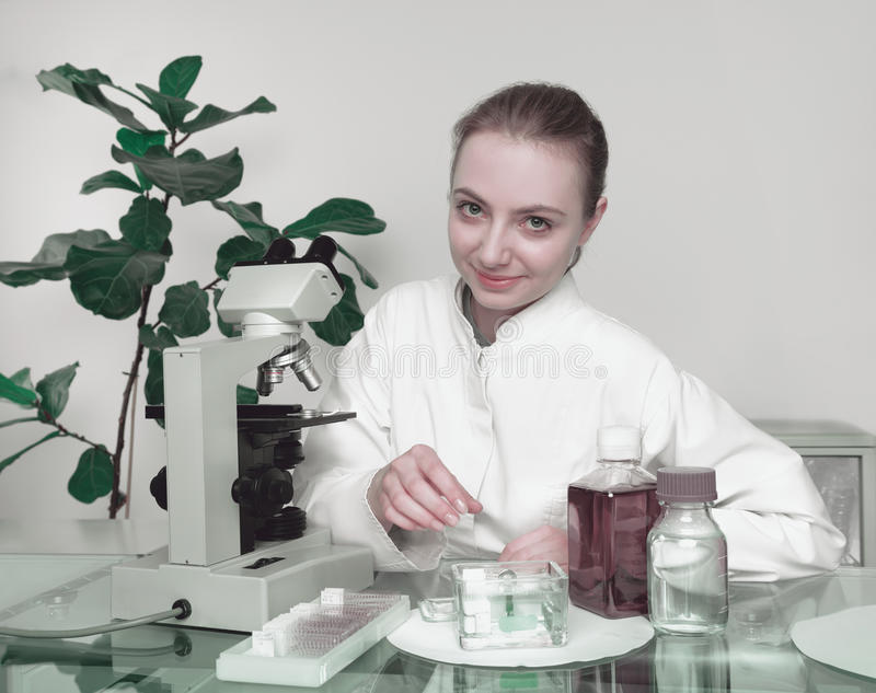 Νέα θηλυκά microscopist χαμόγελα στο θεατή στοκ εικόνες με δικαίωμα ελεύθερης χρήσης
