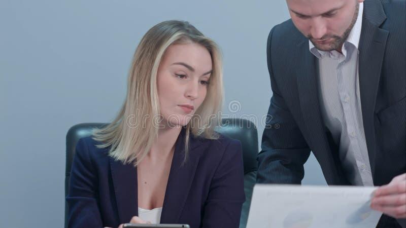 Νέα θηλυκή κύρια συνεδρίαση στον εργασιακό χώρο και το έγγραφο ανάγνωσης με τον καυκάσιο συνάδελφο στην αρχή στοκ εικόνα με δικαίωμα ελεύθερης χρήσης