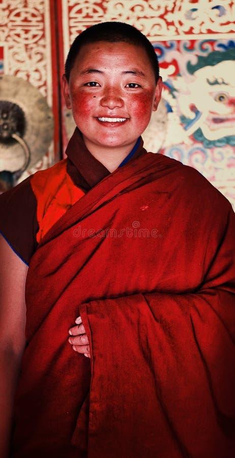 νέα θιβετιανή βουδιστική καλόγρια μπροστά από έναν ιδιαίτερα διακοσμημένο τοίχο του μοναστηριού της στοκ φωτογραφίες με δικαίωμα ελεύθερης χρήσης