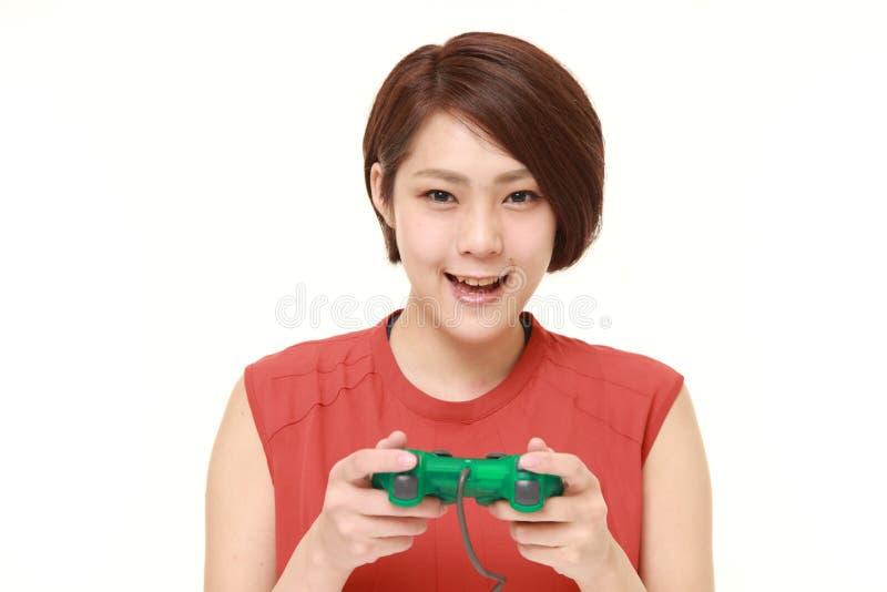 Νέα ιαπωνική γυναίκα που απολαμβάνει ένα τηλεοπτικό παιχνίδι στοκ φωτογραφία