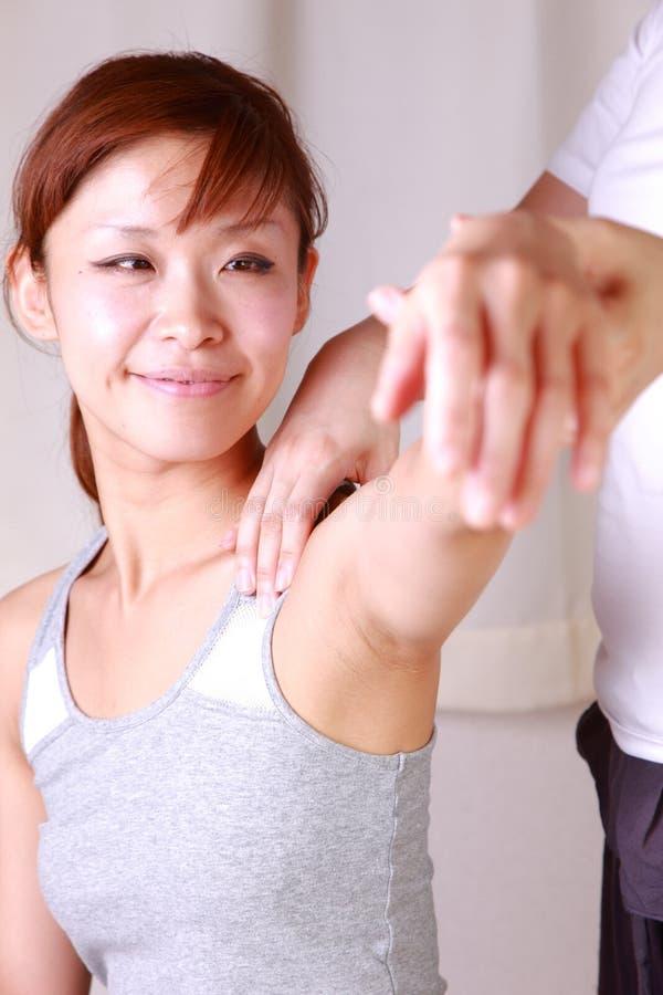 Νέα ιαπωνική γυναίκα που παίρνει chiropractic στοκ φωτογραφία με δικαίωμα ελεύθερης χρήσης