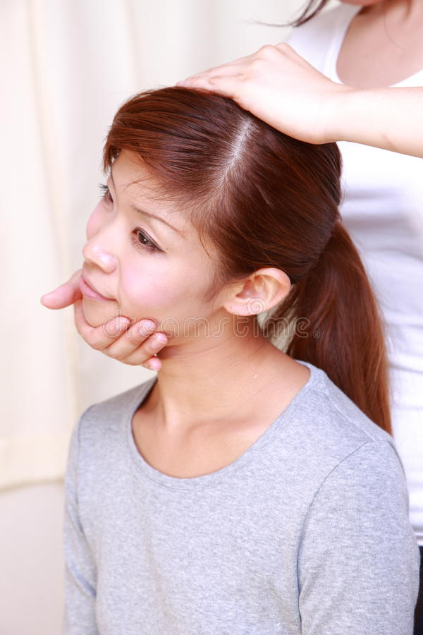 Νέα ιαπωνική γυναίκα που παίρνει chiropractic στοκ εικόνα