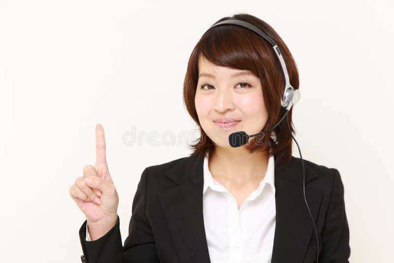 Νέα ιαπωνική επιχειρηματίας που παρουσιάζει και που παρουσιάζει κάτι στοκ εικόνες