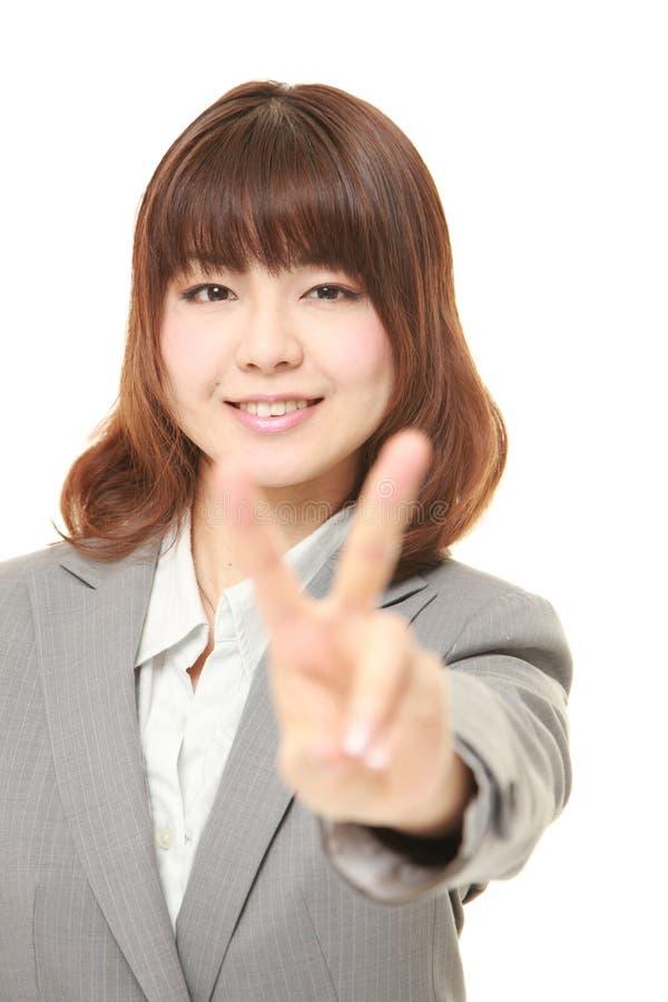 Νέα ιαπωνική επιχειρηματίας που παρουσιάζει σημάδι νίκης στοκ φωτογραφίες