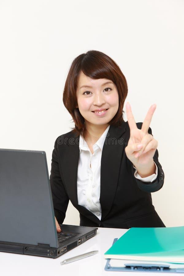 Νέα ιαπωνική επιχειρηματίας που παρουσιάζει σημάδι νίκης στοκ φωτογραφία με δικαίωμα ελεύθερης χρήσης