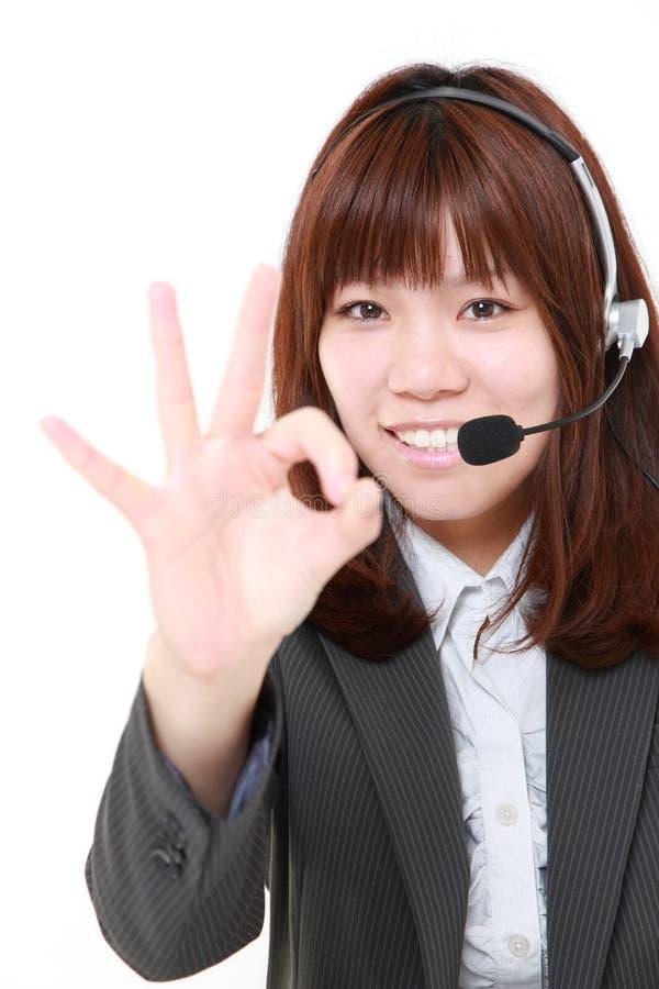 Νέα ιαπωνική επιχειρηματίας του τηλεφωνικού κέντρου με το κεφάλι sets  που παρουσιάζει τέλειο σημάδι στοκ φωτογραφία