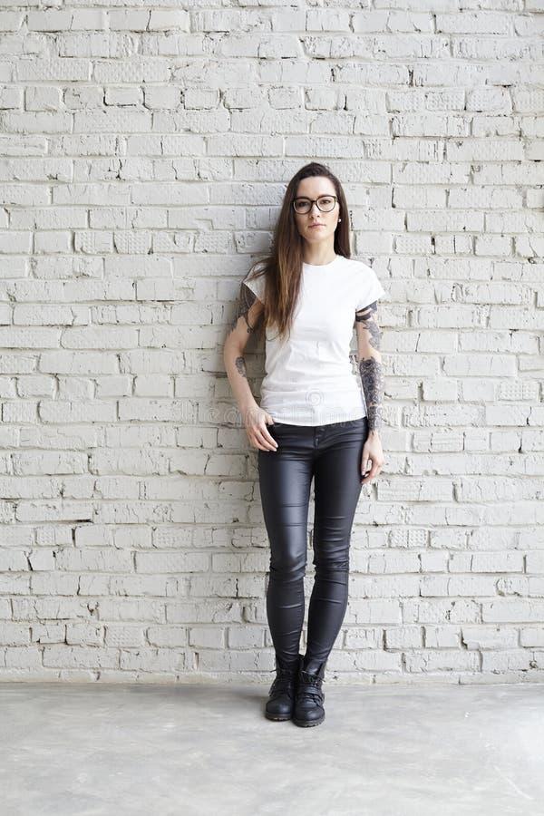 Νέα διαστισμένη γυναίκα που φορά την κενή μπλούζα, που στέκεται μπροστά από το τουβλότοιχο στη σοφίτα στοκ φωτογραφία με δικαίωμα ελεύθερης χρήσης