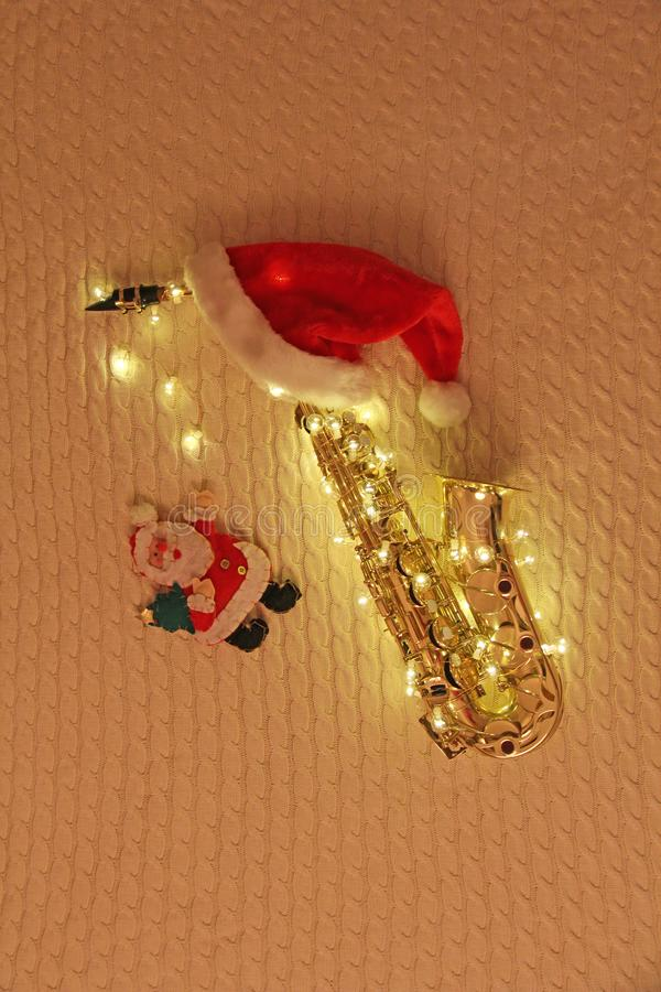 Νέα κάρτα έτους ` s - saxophone, γιρλάντα, Άγιος Βασίλης, κόκκινη ΚΑΠ στοκ εικόνες