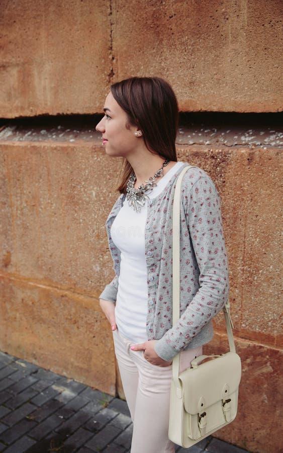Νέα καθιερώνουσα τη μόδα γυναίκα πέρα από το υπόβαθρο τοίχων πετρών στοκ φωτογραφία με δικαίωμα ελεύθερης χρήσης
