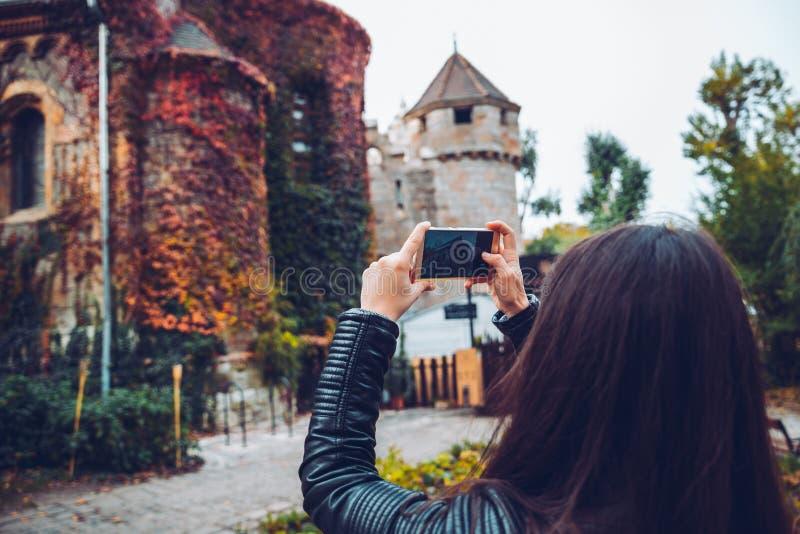 Νέα και ευτυχής γυναίκα τουριστών που κάνει τη φωτογραφία του παλαιού κάστρου στοκ φωτογραφία