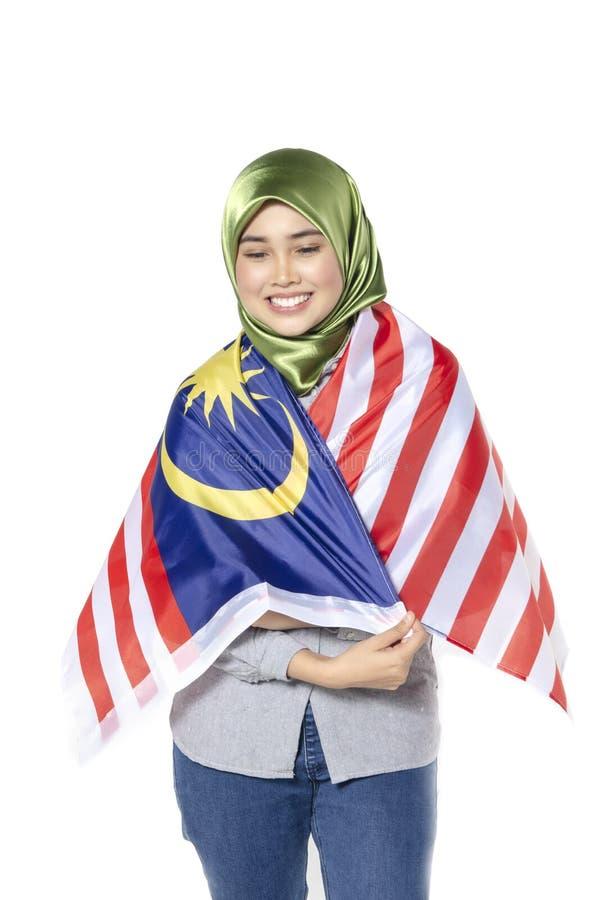 Νέα και όμορφη γυναίκα με τη μαλαισιανή σημαία που απομονώνεται στη λευκιά ΤΣΕ στοκ φωτογραφία με δικαίωμα ελεύθερης χρήσης