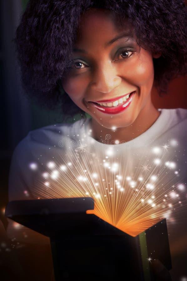 νέα και όμορφη γυναίκα που ανοίγει ένα μαγικό κιβώτιο δώρων στοκ εικόνες