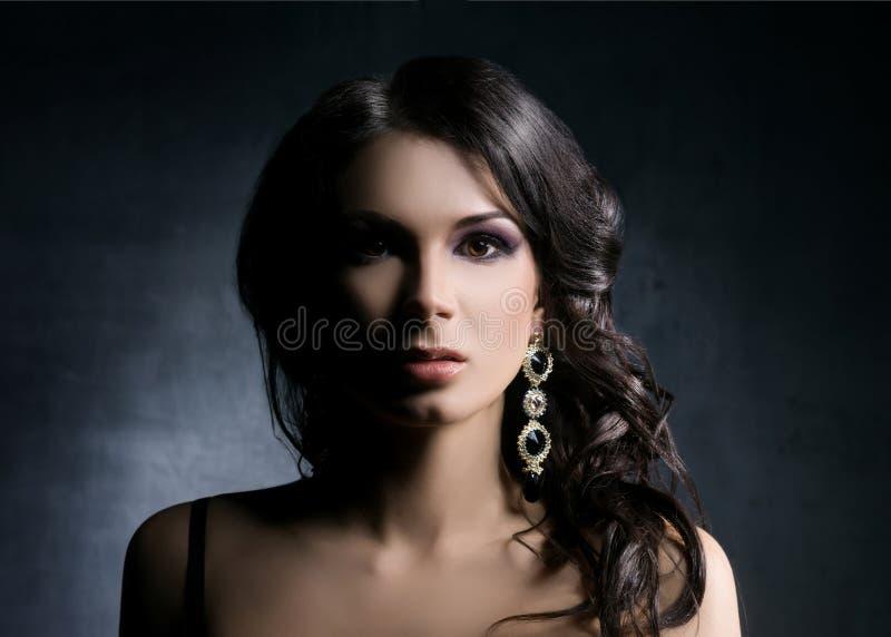 Νέα και όμορφη γυναίκα στα κοσμήματα πέρα από το σκοτεινό υπόβαθρο στοκ φωτογραφίες