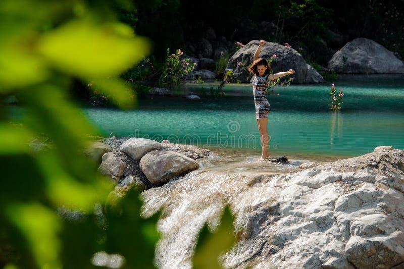 Νέα και όμορφη ευτυχής γυναίκα στο φόρεμα που στέκεται το νερό του τρόπου Lycian στοκ εικόνα