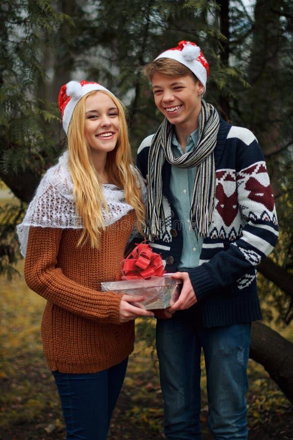 Νέα καπέλα Santa ζευγών ερωτευμένα φορώντας, που κρατούν το α στοκ εικόνα
