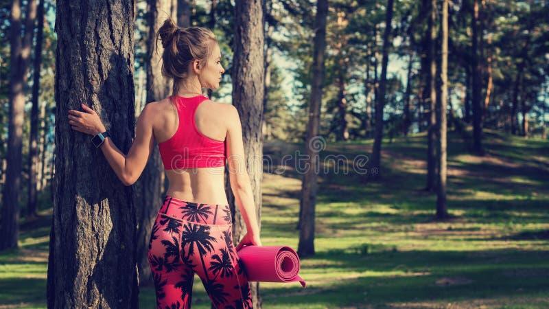 Νέα κατάλληλη αθλητική γυναίκα σε ένα δάσος που φορά το έξυπνο ρολόι και που κρατά το χαλί γιόγκας Μυαλό και έννοια σωμάτων με το στοκ φωτογραφία με δικαίωμα ελεύθερης χρήσης