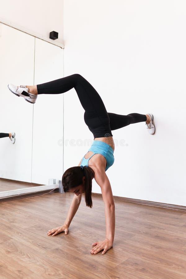 Νέα κατάλληλη γυναίκα που κάνει handstand την άσκηση στη γυμναστική στοκ εικόνα