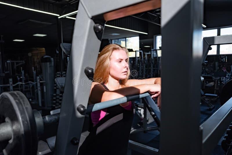 Νέα κατάλληλη γυναίκα που στέκεται στη γυμναστική μπροστά από το barbell θηλυκό στοκ εικόνες