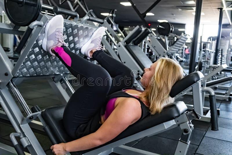 Νέα κατάλληλη γυναίκα στη γυμναστική που κάνει την άσκηση μυών ποδιών με τις δημόσιες σχέσεις ποδιών στοκ εικόνες
